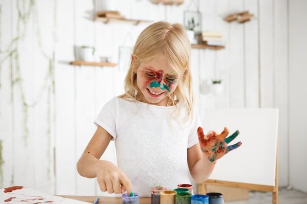 Lachend blondemeisje in wit t-shirt met verf op haar gezicht en handen die door creatieve impuls worden gevangen. kind genieten van kunst.