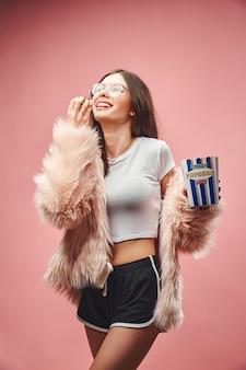 Lachend brunette meisje in roze nepbont met popcorn in de hand, gekleed in zwarte korte broek, witte top en...
