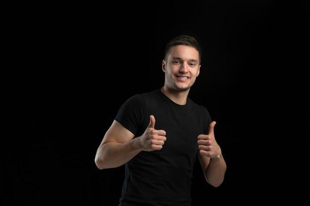 Lachend, duimen omhoog. zwart-wit portret van jonge blanke man geïsoleerd op zwarte studio muur.