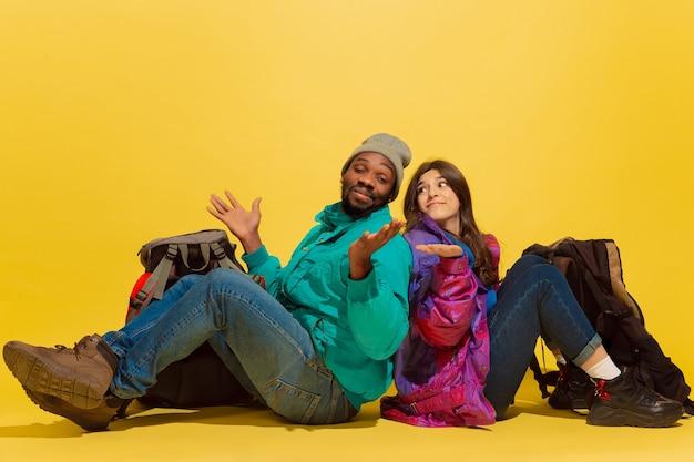 Lachend. echte vrienden. portret van een vrolijk jong toeristenpaar met zakken dat op gele studioachtergrond wordt geïsoleerd. voorbereiden op reizen. resort, menselijke emoties, vakantie, vriendschap, liefde.