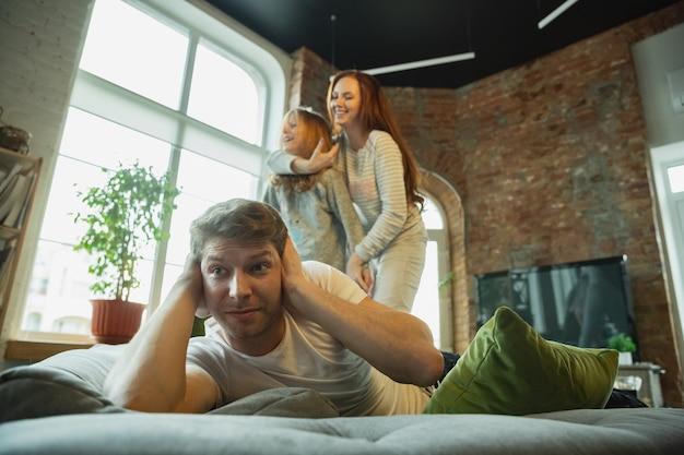 Lachend. familie die thuis leuke tijd samen doorbrengt, ziet er gelukkig en vrolijk uit. moeder, vader en dochter hebben plezier, vechten met kussens. saamhorigheid, thuiscomfort, liefde, relatiesconcept.