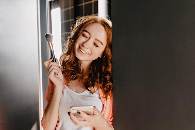 Lachend gembermeisje dat make-up doet. binnen portret van aantrekkelijke jonge vrouw met cosmetische borstel.