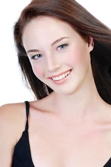Lachend gezicht van jonge mooie tiener geschoten op witte muur