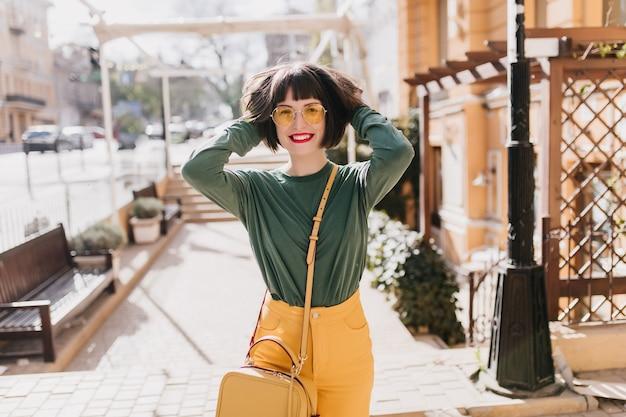 Lachend gracieus meisje speelt met haar korte bruine haar. outdoor portret van prachtige witte vrouw in casual kleding.