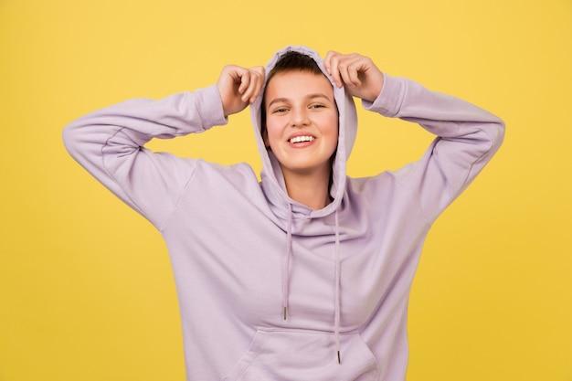 Lachend. het portret van het kaukasische meisje dat op gele studioachtergrond met copyspace voor advertentie wordt geïsoleerd. mooi vrouwelijk model in hoodie. concept van menselijke emoties, gezichtsuitdrukking, verkoop, advertentie, mode.