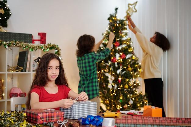 Lachend hispanic meisje inwikkeling presenteert wanneer haar vrienden kerstboom versieren op achtergrond