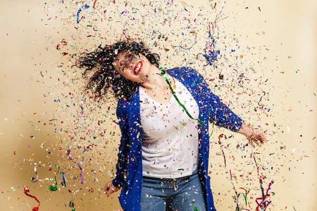 Lachend jong brunette meisje besprenkeld met confetti. feestelijke stemming. nieuwjaar en kerstmis. gele achtergrond.