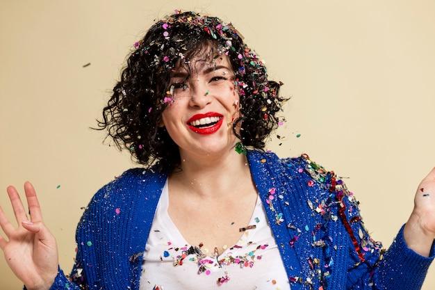 Lachend jong brunette meisje besprenkeld met confetti. feestelijke stemming. nieuwjaar en kerstmis.