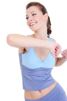 Lachend jong meisje dat lichamelijke oefening doet die op wit wordt geïsoleerd