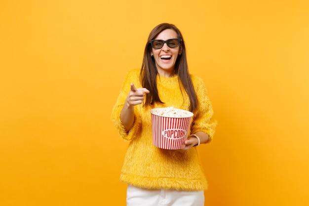 Lachend jong meisje in 3d imax-bril die wijsvinger wijst, filmfilm kijkt, emmer popcorn vasthoudt die op felgele achtergrond wordt geïsoleerd. mensen oprechte emoties in de bioscoop, lifestyle concept.