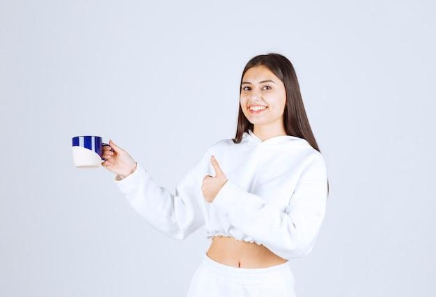 Lachend jong meisje met een kopje en een duim opdagen op wit-grijze achtergrond.