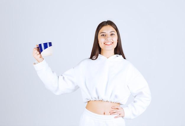 Lachend jong meisje met een kopje op wit-grijze achtergrond.