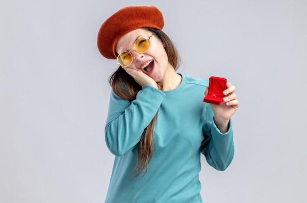 Lachend jong meisje op valentijnsdag met hoed met bril die trouwring vasthoudt en hand op de wang zet die op een witte achtergrond wordt geïsoleerd