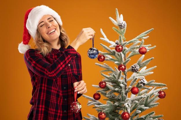 Lachend jong mooi meisje dat in de buurt van de kerstboom staat en een kerstmuts draagt, versier de kerstboom, versier de boom geïsoleerd op een oranje achtergrond