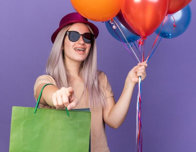 Lachend jong mooi meisje met een beugel en een feestmuts met een bril met ballonnen met een cadeauzakje dat je gebaar laat zien dat op een blauwe muur wordt geïsoleerd