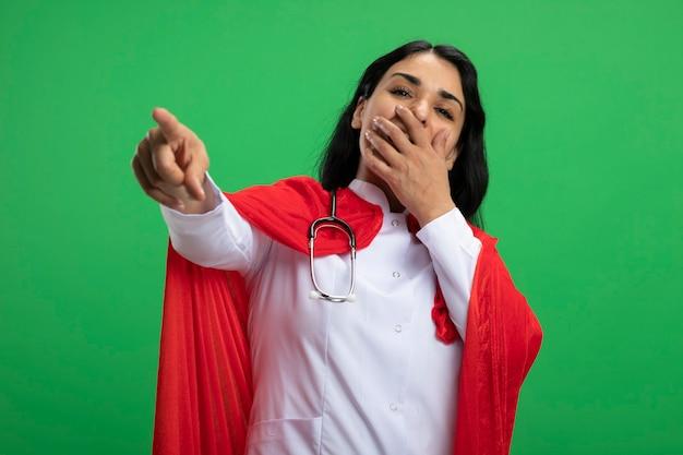 Lachend jong superheldmeisje die medische robe met stethoscoop dragen die u gebaar en behandelde die mond met hand tonen die op groen wordt geïsoleerd