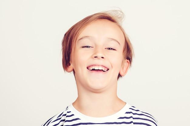 Lachend kind. gelukkige jeugd en positieve emoties. portret van schattige knappe jongen. glimlachende jongen die zich voordeed in de studio. kinderen stijl en mode.
