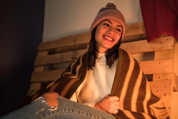 Lachend latina meisje met een winterhoed en een gescheurde spijkerbroek, gewikkeld in een winterdeken met een pallet erachter