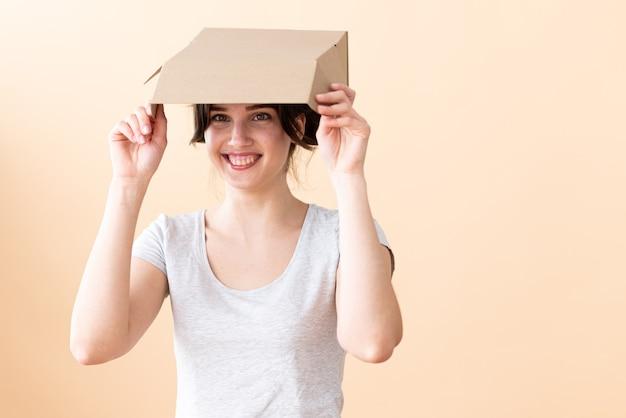 Lachend meisje dat een open kartonnen doos boven haar hoofd houdt, zich verstopt voor de brandende zon of reclame maakt voor haar favoriete leverancier