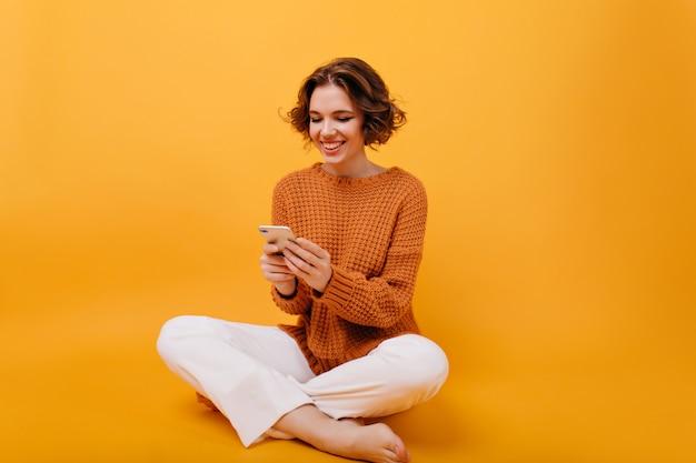 Lachend meisje in casual outfit zitten met gekruiste benen en telefoon vast te houden