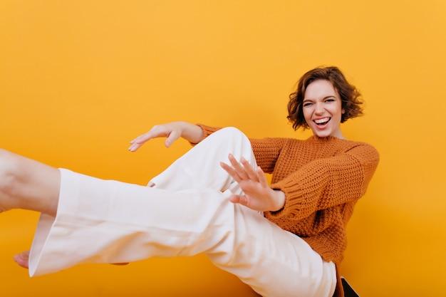 Lachend meisje in een stijlvolle witte broek echte positieve emoties uitdrukken