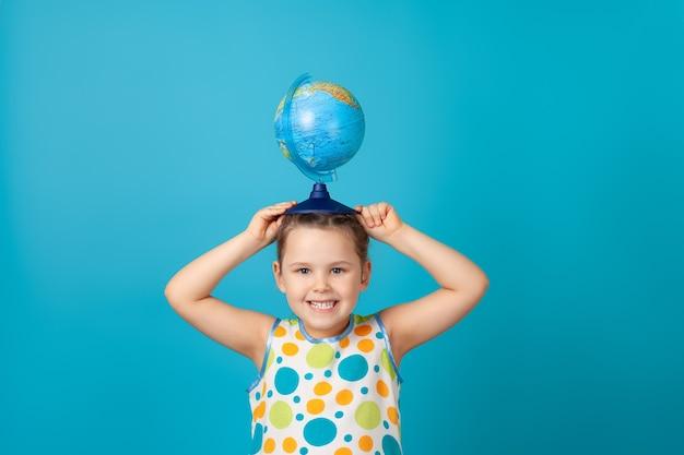 Lachend meisje in een witte zomerjurk met een wereldbol op haar hoofd als een hoed
