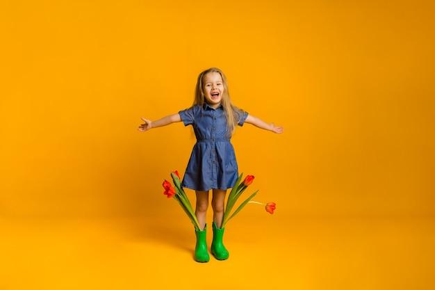 Lachend meisje in groene rubberen laarzen met rode tulpen staat met haar armen gestrekt op een gele muur