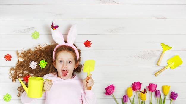 Lachend meisje in konijnoren die op de houten vloer liggen. gelukkige pasen, moedersdag, kinderjarenconcept.