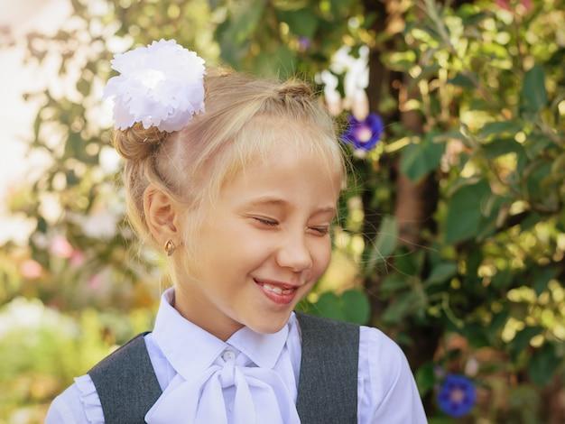 Lachend meisje in schooluniform met strik op haar hoofd in de herfst park.