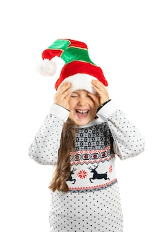 Lachend meisje in witte gebreide kerst trui met rendieren spelen met dwerg hoed geïsoleerd op wit...