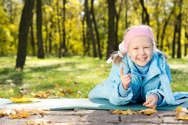 Lachend meisje liggend op de grond op een mat in bos wijzend op de camera met haar vinger