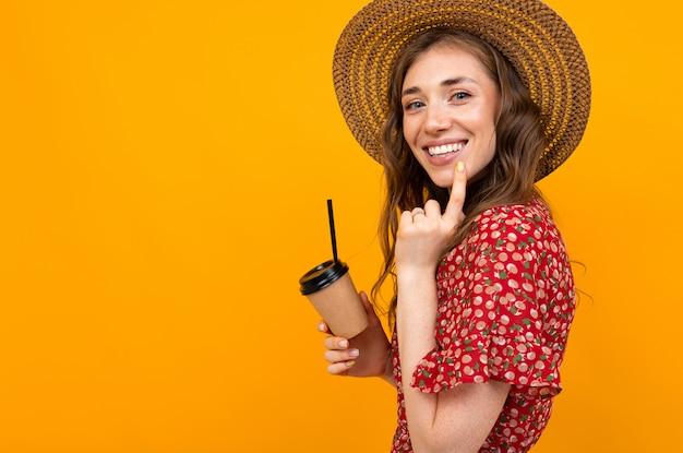 Lachend meisje met koffie op een gele achtergrond in een rode jurk