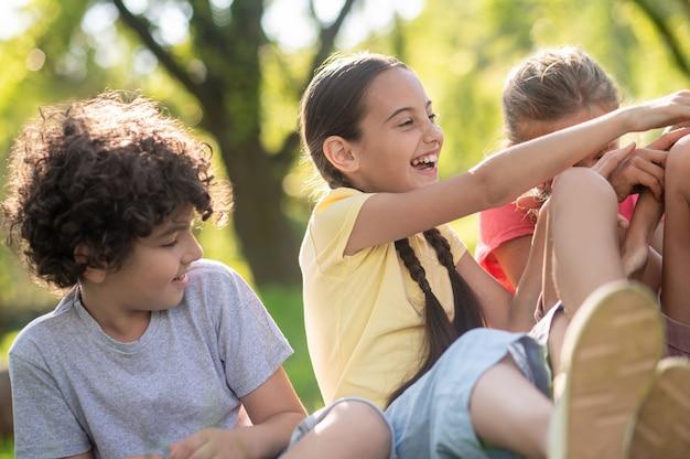 Lachend meisje met vlechten en vrienden in park