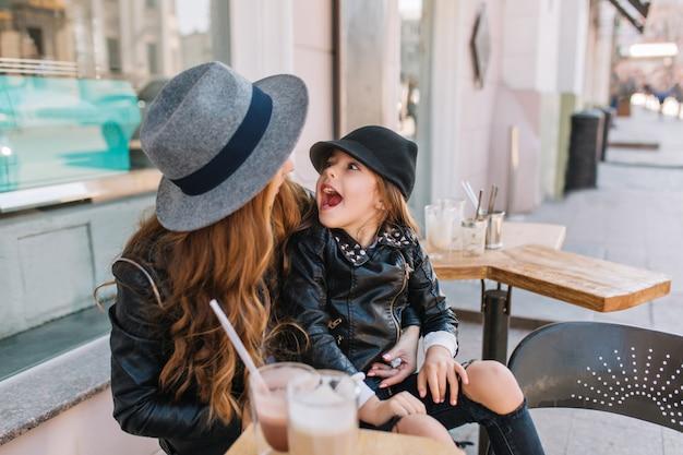 Lachend meisje met zwarte hoed en jas die op mama's knieën rust en gek rond.