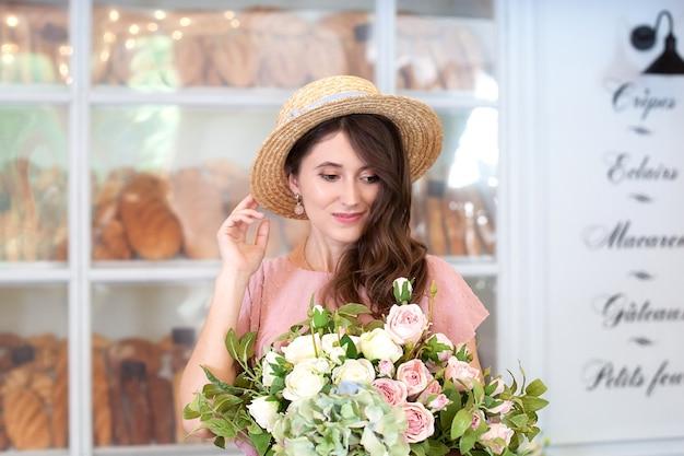 Lachend meisje staat bij raambakkerij in strohoed met een boeket bloemen als verrassingscadeau with