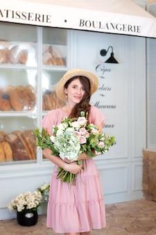 Lachend meisje staat in de buurt van raambakkerij in strohoed met een boeket bloemen cadeau