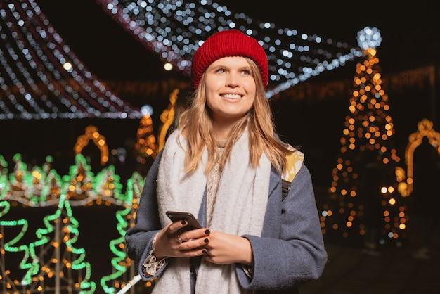 Lachend meisje verliefd op kerstverlichting terwijl ze haar telefoon vasthoudt, 's nachts, op straat.