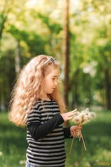 Lachend meisje verzamelt witte paardebloemen in een park in de zomer. verticaal