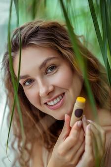Lachend meisje. vrij jonge vrouw die een stok van lippenbalsem houdt en glimlacht
