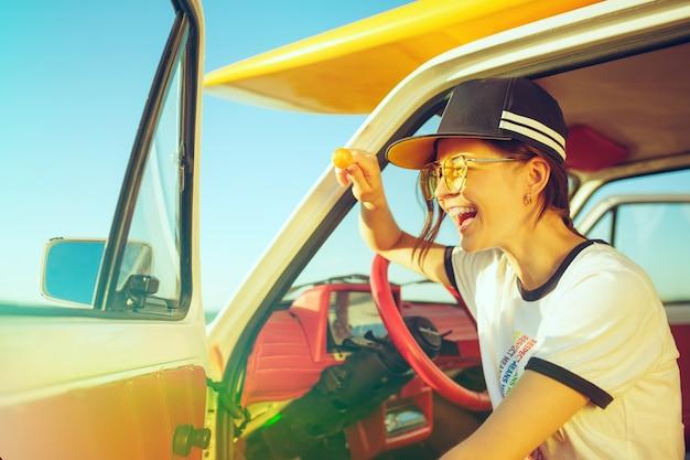 Lachend meisje zit in de auto tijdens een road trip in de buurt van de rivier