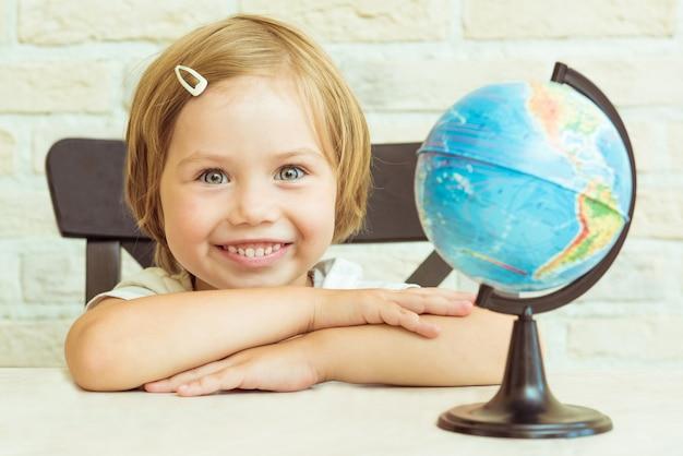 Lachend meisje zit in de buurt van de wereld. ze vouwde haar handen