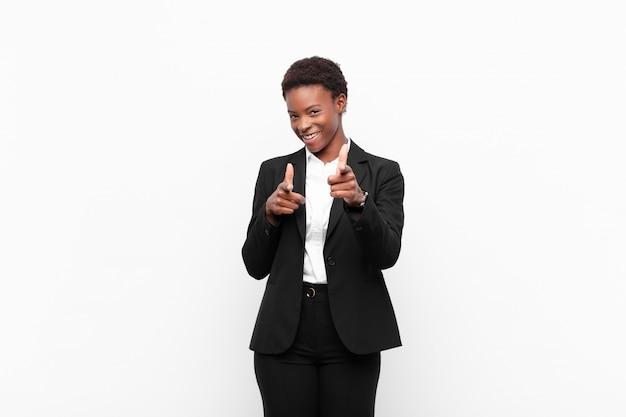 Lachend met een positieve, succesvolle, gelukkige houding wijzend, geweer teken makend met handen