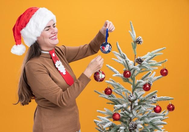 Lachend met gesloten ogen jong mooi meisje met kerstmuts met stropdas staande in de buurt van kerstboom met kerst bal geïsoleerd op oranje muur