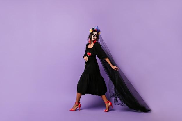 Lachend mexicaans model in halloween-outfit loopt door lila muur, met lange zwarte sluier vast.