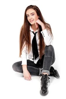Lachend model met lang haar in wit overhemd en stropdas geïsoleerd op een witte achtergrond