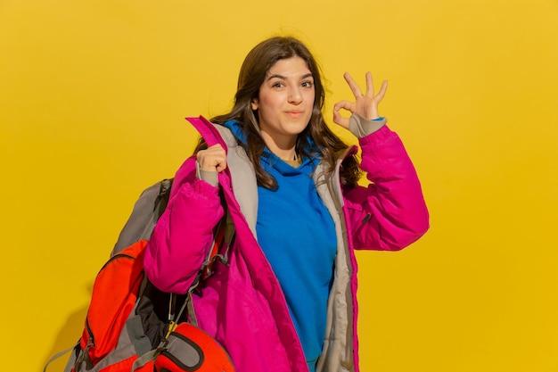 Lachend, mooie shows. portret van een vrolijk jong kaukasisch toeristenmeisje met zak en verrekijker dat op gele studioachtergrond wordt geïsoleerd.