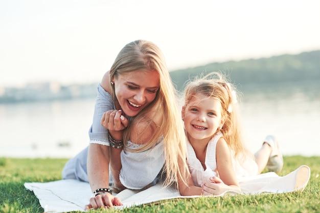 Lachend naar de camera. foto van jonge moeder en haar dochter die goede tijd hebben op het groene gras met meer bij achtergrond.