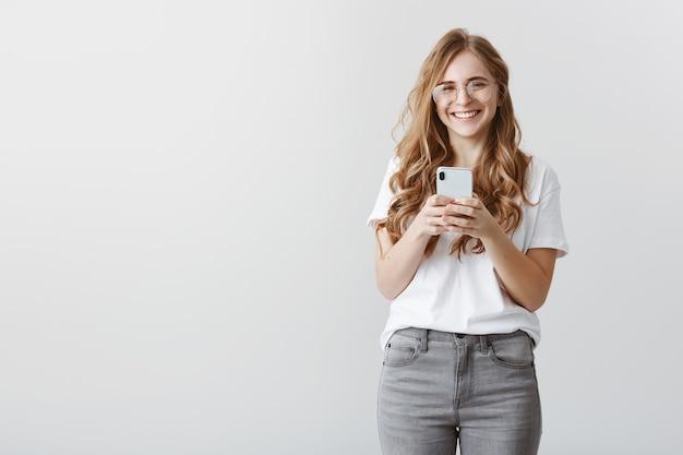 Lachend om de foto die het meisje maakte. portret van gelukkige aantrekkelijke kaukasische vrouwelijke blogger in glazen en trendy outfit met smartphone, grinnikend van positieve emoties