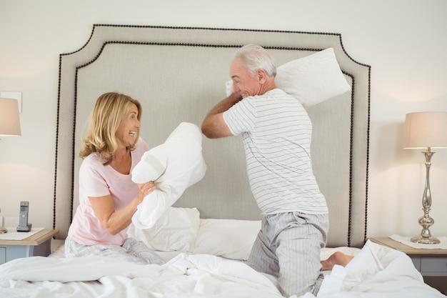 Lachend paar dat hoofdkussenstrijd op bed heeft