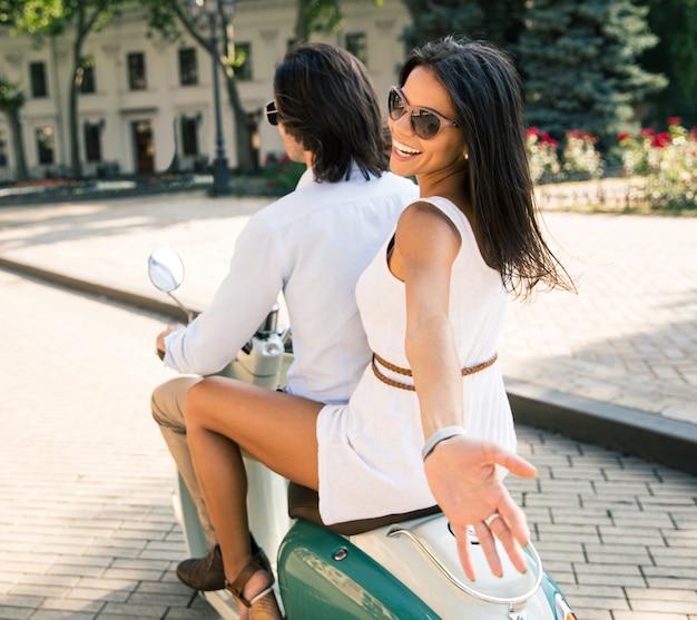 Lachend paar rijden op een scooter